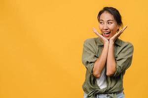 Retrato de joven asiática con expresión positiva, sonrisa amplia, vestida con ropa casual sobre fondo amarillo. feliz adorable mujer alegre se regocija con el éxito. concepto de expresión facial. foto