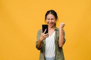 Sorprendió a la joven asiática que usa el teléfono móvil con expresión positiva, sonríe ampliamente, vestida con ropa informal y está aislada sobre fondo amarillo. feliz adorable mujer alegre se regocija con el éxito. foto