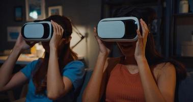 Attractive Asia ladies enjoy happy moment shopping online experience with virtual reality glasses headset site on couch living room in home at dark night. Using with VR goggles headset for movie time. photo