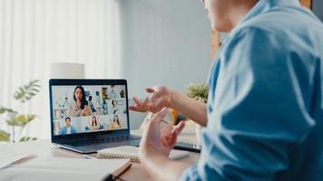 joven empresario de asia usando laptop hablar con colegas sobre el plan en la reunión de videollamada mientras trabaja desde casa en la sala de estar. autoaislamiento, distanciamiento social, cuarentena para la prevención del coronavirus. foto