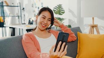 hermosa dama asiática sonriendo y sentada en el sofá llamada telefónica hablar saluda con la familia en casa. quedarse en casa, relación a larga distancia, relación familiar, mantener la distancia, concepto de cuarentena covid. foto