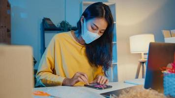 Young Asia businesswoman wear face mask check purchase order on smartphone and stock in computer in home office at night. Small business owner, online market delivery, lifestyle freelance concept. photo