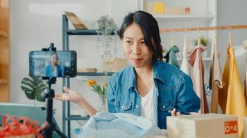 Joven diseñadora de moda asiática usando un teléfono móvil recibiendo una orden de compra y mostrando ropa grabando video en vivo en línea en la tienda. propietario de una pequeña empresa, concepto de entrega de mercado en línea. foto