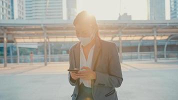 Joven empresaria asiática en ropa de oficina de moda usa mascarilla médica usando el teléfono mientras camina sola al aire libre en una ciudad urbana. negocio en marcha, distanciamiento social para evitar la propagación del concepto covid-19. foto