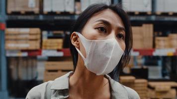 Gerente de joven empresaria de Asia usar mascarilla en busca de productos mediante tableta digital que controla los niveles de inventario de pie en el centro comercial minorista. distribución, logística, paquetes listos para embarque. foto