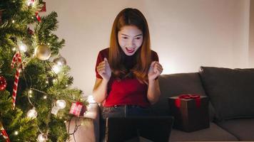 Mujer joven de Asia con videollamada de tableta hablando con pareja, árbol de Navidad decorado con adornos en el sofá en la sala de estar en casa. distanciamiento social, noche de navidad y fiesta de fin de año. foto