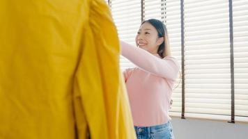 Beautiful attractive young Asia lady choosing her fashion outfit clothes in closet at house or store. Girl think what to wear casual shirt. Home wardrobe or clothing shop changing room. photo