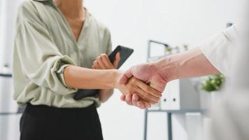 Multiracial group of young creative people in smart casual wear discussing business shaking hands together and smiling while standing in modern office. Partner cooperation, coworker teamwork concept. photo