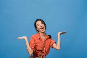 Retrato de joven asiática sonriendo con expresión alegre, muestra algo sorprendente en el espacio en blanco en un paño casual y mirando a cámara aislada sobre fondo azul. concepto de expresión facial. foto
