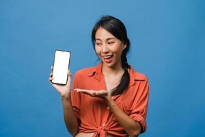 Joven asiática muestra la pantalla vacía del teléfono inteligente con expresión positiva, sonríe ampliamente, vestida con ropa casual sintiendo felicidad sobre fondo azul. teléfono móvil con pantalla en blanco en mano femenina. foto
