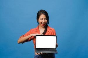 Young Asia lady show empty laptop screen with positive expression, smiles broadly, dressed in casual clothing feeling happiness isolated on blue background. Computer with white screen in female hand. photo