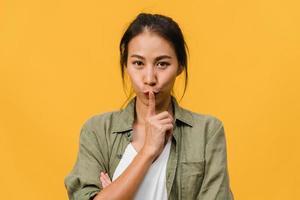 Retrato de joven asiática con expresión positiva, piensa en las próximas vacaciones, vestida con ropa casual y mirando a cámara sobre fondo amarillo. feliz adorable mujer alegre se regocija con el éxito. foto