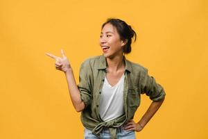 Retrato de joven asiática sonriendo con expresión alegre, muestra algo sorprendente en el espacio en blanco en ropa casual y de pie aislado sobre fondo amarillo. concepto de expresión facial. foto