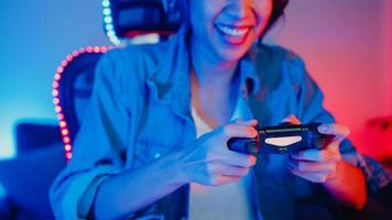 Happy asia girl gamer wear headphone set and joystick controller talk with friend feel fun and excited with competition online game in neon living room home studio at night, Home quarantine activity. photo