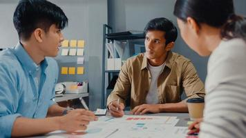Happy young Asia businessmen and businesswomen meeting brainstorming some new ideas about project to his partner working together planning success strategy enjoy teamwork in small modern home office. photo