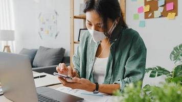 Freelancer Asia women wear face mask using smartphone shopping online via website while sitting at desk in living room. Working from home, remotely work, social distancing, quarantine for coronavirus. photo