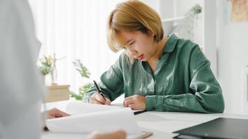 Paciente femenina joven de Asia que firma el formulario médico o el acuerdo de seguro médico de la firma en la reunión en la clínica con la doctora en uniforme médico blanco sentada en el escritorio en la oficina del hospital de salud. foto