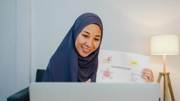 Asia dama musulmana usa hijab usando computadora portátil, hable con su colega sobre el plan en una reunión de videollamada mientras trabaja de forma remota desde casa por la noche en la sala de estar. distanciamiento social, cuarentena por coronavirus. foto