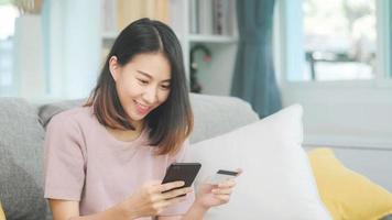 Joven mujer asiática sonriente con smartphone comprando compras en línea con tarjeta de crédito mientras está acostado en el sofá cuando se relaja en la sala de estar en casa. estilo de vida de las mujeres de etnia latina e hispana en el concepto de casa. foto