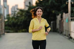 Beautiful young Asia athlete lady running exercises work out in urban environment. Japanese teen girl wearing sports clothes on walkway bridge in early morning. Lifestyle active sporty in city. photo