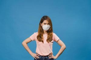 Joven asiática usa mascarilla médica con expresión negativa, grito emocionado, llorando emocionalmente enojado y mira a cámara aislada sobre fondo azul. distanciamiento social, cuarentena por coronavirus. foto