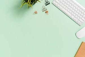 espacio de trabajo mínimo: foto creativa plana del escritorio del espacio de trabajo. escritorio de oficina de vista superior con teclado, mouse y libro sobre fondo de color verde pastel. vista superior con espacio de copia, fotografía plana.