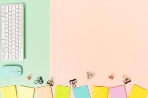 espacio de trabajo mínimo: foto creativa plana del escritorio del espacio de trabajo. Escritorio de oficina de vista superior con teclado, mouse y nota adhesiva sobre fondo de color rosa verde pastel. vista superior con fotografía de espacio de copia.