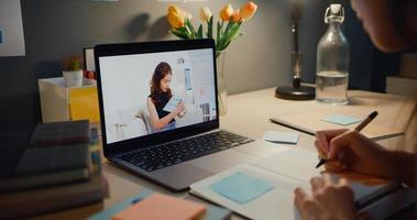 joven estudiante de asia adolescente lección de aprendizaje a distancia con el profesor en línea y estudio en la pantalla del portátil en la sala de estar en casa por la noche. a distancia, distanciamiento social, cuarentena para la prevención del coronavirus. foto