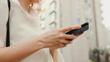 Exitosa empresaria asiática joven en ropa de oficina de moda usando teléfonos inteligentes y escribiendo mensajes de texto mientras camina sola al aire libre en la ciudad moderna urbana por la mañana. concepto de negocio en movimiento. foto