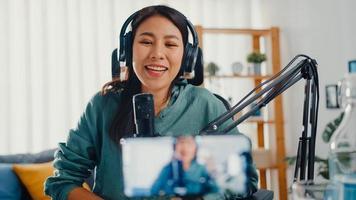 Influencer adolescente de asia usa micrófono usa auriculares graba contenido con teléfono inteligente para audiencia en línea escuchar en casa. estudiante de podcasts hace podcasts de audio desde el estudio de su casa. foto