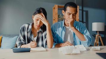 Stress asia couple man and woman use calculator for calculate family budget, debts, monthly expenses during financial economic crisis at home. marriage money trouble, Family budget planning concept. photo