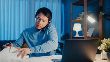 El joven empresario asiático usa el papeleo de la asignación de la agenda de la reunión de la llamada del teléfono inteligente con un colega que mira la computadora portátil en la sala de estar en casa horas extras por la noche, trabaja desde el hogar concepto de pandemia de corona. foto