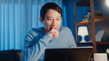 Asia empresario se centra en la asignación de la reunión de videollamadas en línea en el papeleo con un colega en la computadora de la tableta en la sala de estar en casa horas extras por la noche, trabaja desde el hogar concepto de pandemia de coronavirus. foto