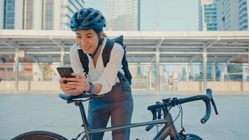 Sonrisa empresaria asiática con mochila uso cámara de mirada de teléfono inteligente en la ciudad de pie en la calle con bicicleta ir a trabajar en la oficina. chica deportiva usa el teléfono para el trabajo. viaje diario al trabajo, viajero de negocios en la ciudad. foto