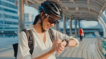empresaria asiática con mochila bicicleta sonriendo mirar smartwatch en la calle de la ciudad ir a trabajar en la oficina. chica deportiva usa su aplicación de reloj para realizar un seguimiento de la actividad física. viaje diario al trabajo, viajero de negocios en la ciudad. foto