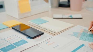 Joven empresaria asiática utiliza un teléfono inteligente con una pantalla en blanco en negro simulado para mostrar texto publicitario mientras trabaja de manera inteligente desde casa en la sala de estar. tecnología chroma key, concepto de diseño de marketing. foto