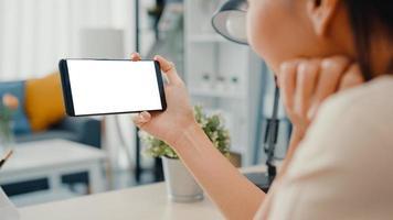 Jovencita asiática usa un teléfono inteligente con una pantalla en blanco en blanco simulado para mostrar texto publicitario mientras trabaja de manera inteligente desde casa en la sala de estar. tecnología chroma key, concepto de diseño de marketing. foto