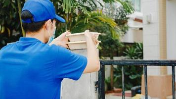 El joven mensajero de entrega postal usa una mascarilla que maneja la caja de alimentos para enviar al cliente en la casa y una mujer asiática recibe el paquete entregado al aire libre. estilo de vida nuevo normal después del concepto del virus corona. foto