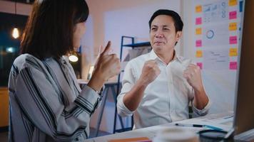 Grupo de empresarios asiáticos y de negocios en discusiones informales sobre negocios celebran dando cinco después de tratar sintiéndose felices y firmando contrato o acuerdo en la oficina nocturna. concepto de trabajo en equipo de compañero de trabajo foto