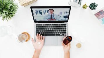 Vista superior de una joven que usa una computadora portátil hablar sobre una enfermedad en una llamada de videoconferencia con una consulta en línea con un médico senior en la sala de estar de su casa. distanciamiento social, cuarentena por coronavirus. foto