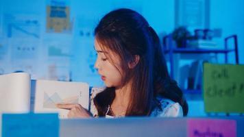 Asia empresaria distanciamiento social en la nueva normalidad para la prevención de virus mirando la presentación de la cámara a un colega sobre el plan en la videollamada mientras trabaja en la noche de la oficina. estilo de vida después del coronavirus. foto