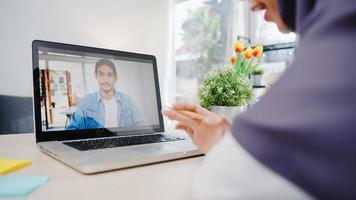 Asia empresaria musulmana que usa una computadora portátil hable con un colega sobre el plan mediante una videollamada para una reunión en línea mientras trabaja de forma remota desde su casa en la sala de estar. distanciamiento social, cuarentena por coronavirus foto