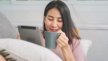 hermosa atractiva mujer asiática sonriente con tableta sosteniendo una taza de café o té caliente mientras está acostado en el sofá cuando se relaja en la sala de estar en casa. mujeres de estilo de vida en el concepto de hogar. foto