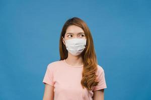 La joven asiática usa una mascarilla médica, cansada del estrés y la tensión, mira con confianza el espacio aislado sobre fondo azul. autoaislamiento, distanciamiento social, cuarentena para la prevención del coronavirus. foto