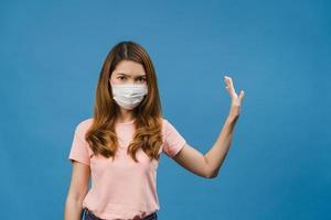 Joven asiática usa mascarilla médica haciendo dejar de cantar con la palma de la mano con expresión negativa y mirando a cámara aislada sobre fondo azul. distanciamiento social, cuarentena por coronavirus. foto