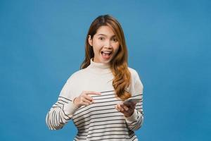Sorprendió a la joven asiática que usa el teléfono móvil con expresión positiva, sonríe ampliamente, vestida con ropa informal y mirando a la cámara sobre fondo azul. feliz adorable mujer alegre se regocija con el éxito. foto