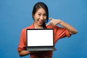 Joven asiática muestra una pantalla de computadora portátil vacía con expresión positiva, sonríe ampliamente, vestida con ropa casual sintiendo felicidad aislada sobre fondo azul. computadora con pantalla blanca en mano femenina. foto