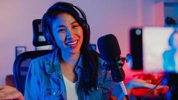 feliz asia chica blogger música influencer uso smartphone transmisión grabación usar auriculares en línea hablar en vivo con audiencia en la sala de estar estudio en casa por la noche. concepto de creador de contenido. foto
