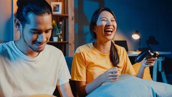 Feliz pareja joven de Asia, hombre y mujer, sentarse en el sofá, usar el controlador de joystick, jugar videojuegos, pasar tiempo divertido juntos en la sala de estar por la noche. estilo de vida familiar de pareja casada asiática, concepto de estancia en casa. foto