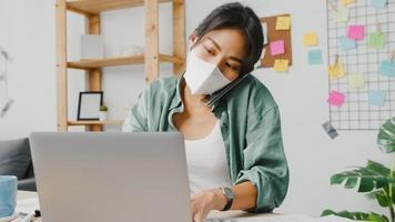 Young Asia women wear medical face mask talking on phone busy entrepreneur working distantly in living room. Working from home, remotely work, social distancing, quarantine for corona virus prevention photo